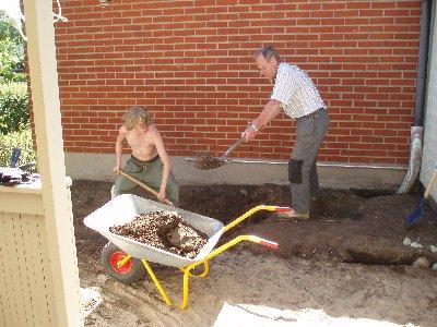 Rune och Calle gräver bort jord och grus